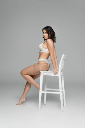 Photo for Gorgeous model in lingerie looking at camera near chair on grey background - Royalty Free Image
