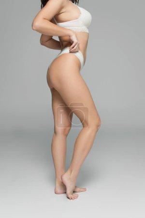 Photo pour Vue recadrée de la femme touchant culotte blanche sur fond gris - image libre de droit