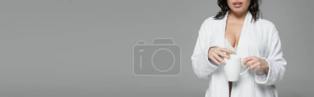Photo for Cropped view of sexy woman in bathrobe holding cup of coffee isolated on grey, banner - Royalty Free Image