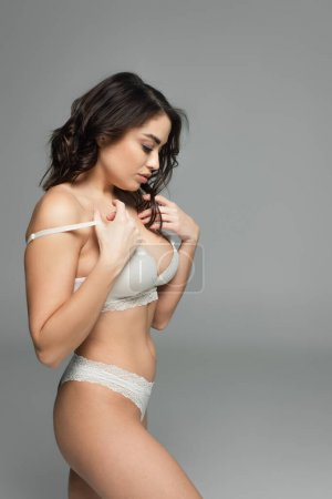 Photo for Side view of sensual woman taking off bra isolated on grey - Royalty Free Image