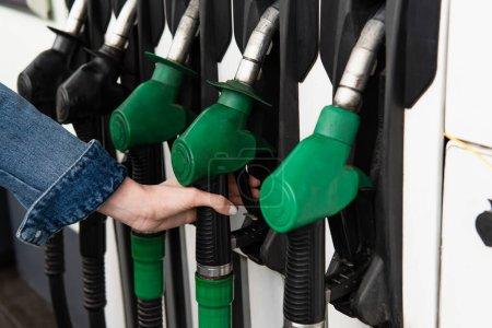 Photo pour Vue partielle de la main féminine près des pistolets à essence sur la station-service - image libre de droit