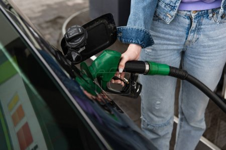 Photo pour Vue recadrée de la femme en jeans ravitaillement voiture sur la station-service - image libre de droit