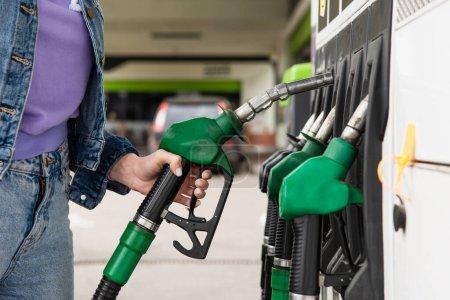 Photo pour Vue recadrée d'une femme vêtue de denim tenant un pistolet à carburant sur une station-service - image libre de droit
