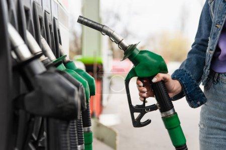 Photo pour Vue recadrée d'une femme tenant un pistolet à essence sur une station-service - image libre de droit