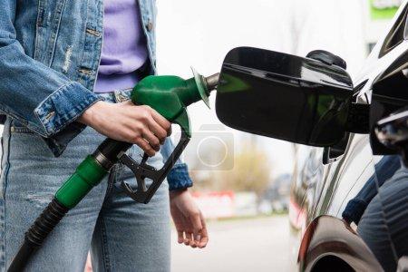 Photo pour Vue partielle de la jeune femme en jeans tenant pistolet à essence près de l'automobile - image libre de droit