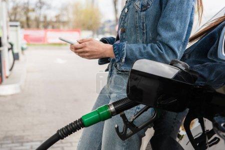 Photo pour Vue partielle de la messagerie jeune femme sur téléphone portable près de la voiture sur la station-service - image libre de droit