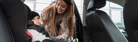 Photo pour Femme heureuse près fils de toddle assis dans la voiture dans le siège bébé, bannière - image libre de droit