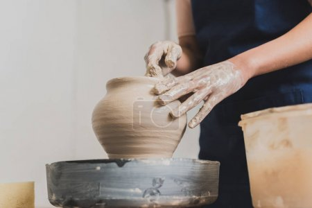 partial view of young african american woman shaping wet clay pot on wheel with hands in pottery