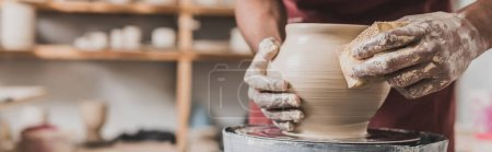 close up view of young african american man holding sponge and making wet clay pot on wheel in pottery, banner