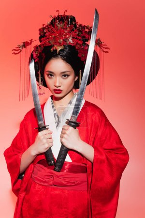 Japanese woman in traditional costume holding swords on red background