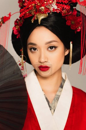 Asian woman with red lips holding black fan isolated on grey