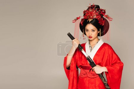 Photo for Japanese woman looking at camera and holding sword isolated on grey - Royalty Free Image