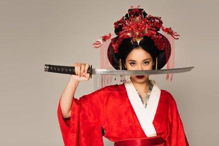 Photo pour Femme japonaise tenant l'épée près du visage isolé sur gris - image libre de droit