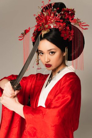Japanese woman with national hairdo holding sword isolated on grey