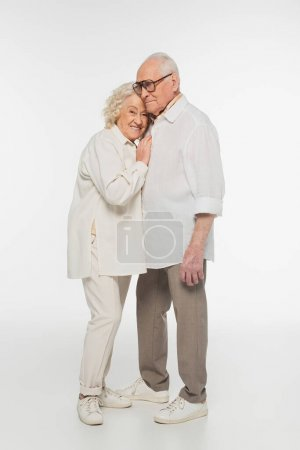 elderly woman gently hugging senior man with hand on breast on white