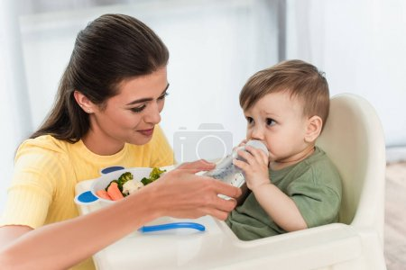 Mother holding baby bottle near son and vegetables on high chair at home