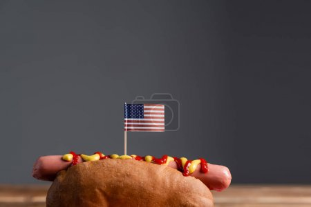 tasty hot dog with small american flag isolated on grey with copy space