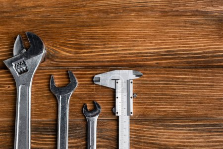 top view of different wrenches and calipers on wooden table, labor day concept