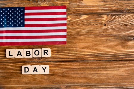 top view of usa flag near cubes with labor day lettering on wooden table