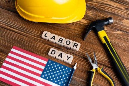 Photo pour Etats-Unis drapeau, marteau, pinces, casque et cubes avec lettrage de la fête du travail sur table en bois - image libre de droit