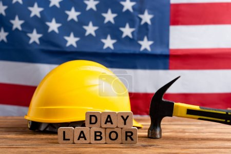 cubes with labor day lettering, hammer and hardhat near usa flag on blurred background