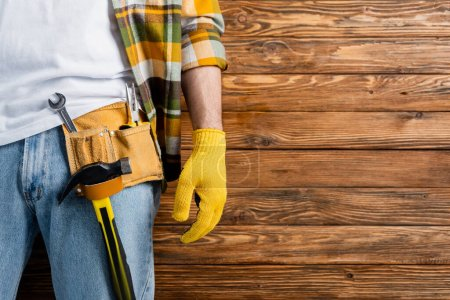 Photo for Cropped view of handyman in tool belt and work glove on wooden background, labor day concept - Royalty Free Image