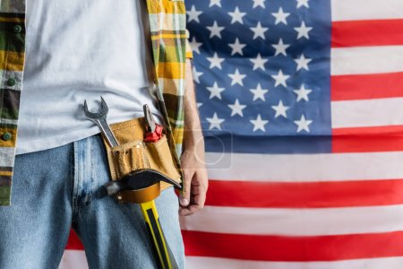 Photo for Partial view of builder in tool belt near usa flag on blurred background, labor day concept - Royalty Free Image
