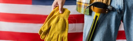 cropped view of workman with hammer in tool belt holding work gloves near usa flag, labor day concept, banner