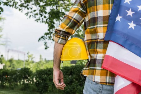 back view of cropped foreman with usa flag and hardhat outdoors, labor day concept