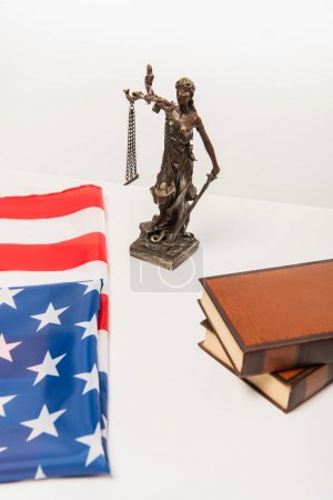 Photo pour Vue en angle élevé de la statuette de justice près du drapeau américain et des livres isolés sur blanc - image libre de droit