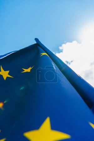 bottom view of blue european union flag against sky with clouds