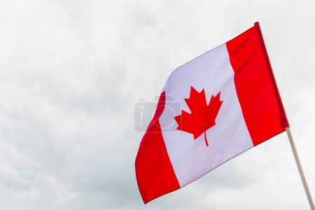 flag of canada with maple leaf against cloudy sky