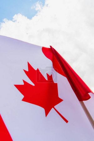 low angle view of flag of canada with maple leaf against sky