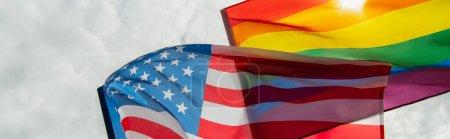 baja vista angular de banderas americanas y lgbt contra el cielo, bandera