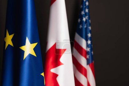 blue european union, canadian and american flags isolated on black