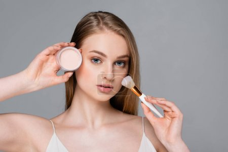 young woman holding cosmetic brush and face powder isolated on gray