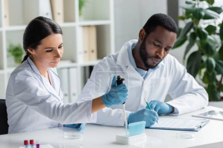 Photo for Scientist holding electronic pipette near test tubes and blurred african american colleague writing on clipboard - Royalty Free Image