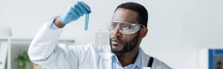 Photo for African american scientist in safety goggles holding test tube, banner - Royalty Free Image