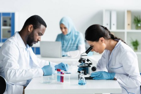 Photo for Multiethnic scientists writing on clipboard and working with microscope in lab - Royalty Free Image