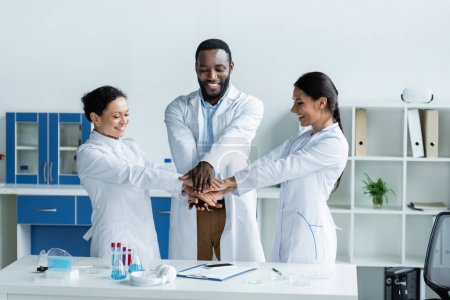 Photo for Smiling interracial scientists holding hands near test tubes and clipboard in laboratory - Royalty Free Image