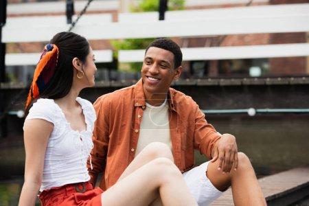 fröhliche gemischtrassige Pärchen reden, während sie auf Straßenrand in der Stadt sitzen
