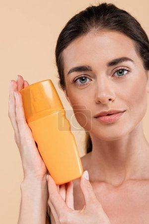 Photo pour Jolie femme montrant bouteille de crème solaire tout en regardant la caméra isolée sur beige - image libre de droit