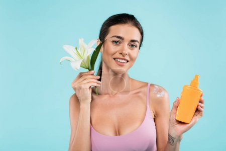 cheerful woman with sunblock and white lily looking at camera isolated on blue