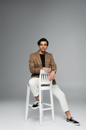 Photo pour Pleine longueur de jeune homme en blazer assis sur chaise blanche sur gris - image libre de droit