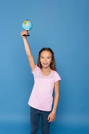 Photo for Happy preteen kid rising globe and looking at camera isolated on blue - Royalty Free Image