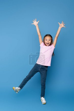 Excited child looking at camera on blue background