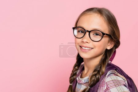 Photo pour Portrait of smiling schoolkid in eyeglasses isolated on pink - image libre de droit