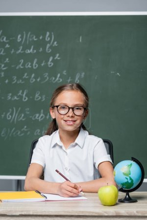 positive schoolgirl with pen smiling at camera near globe and notebook on desk