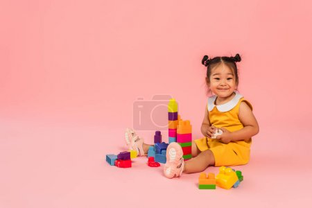 happy asian toddler girl in yellow dress playing building blocks on pink
