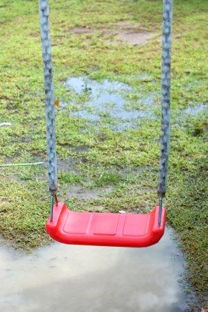 Foto de Red chain swings on modern kids playground in rainy day. - Imagen libre de derechos